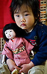 A Japanese girl holds onto to an ornamental doll