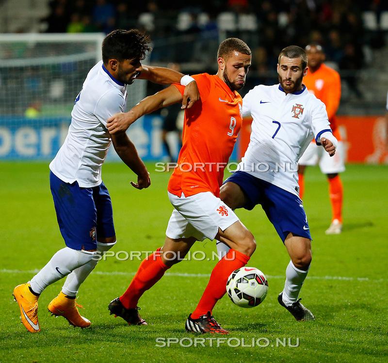 Nederland, Alkmaar, 9 oktober 2014<br /> Play-offs EK-kwalificatie<br /> Jong Oranje-Jong Portugal (0-2)<br /> V.l.n.r.: Ricardo Esgaio van Jong Portugal, Luc Castaignos van Jong Oranje en Rafa van Jong Portugal