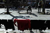 Pictured: Migrants men rest on a bench while their clothes dry on a park railing nearby Friday 26 February 2016<br /> Re: Hundreds of refugees have temporarily camped at Victoria Square in central Athens, Greece.