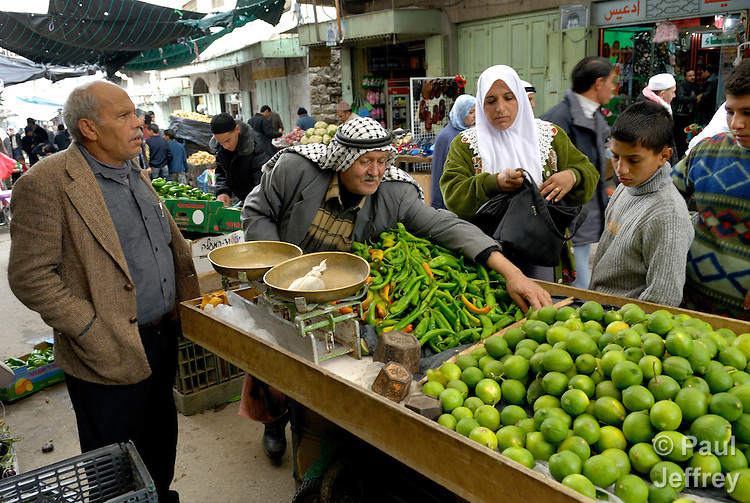 A Palestinian man sells peppers in the market of Hebron, where many shops are boarded up because of Jewish settler violence and the stagnating economy.