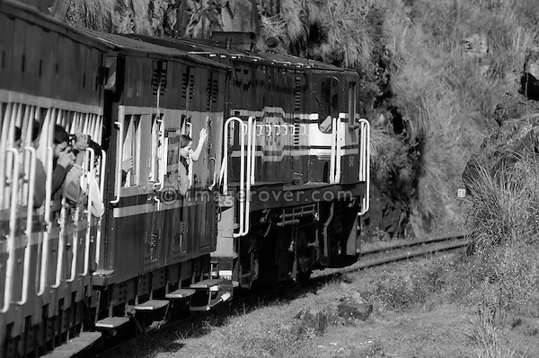 Tourists on the Nilgiri Mountain Railway driving from Ooty to Coonoor. India, Tamil Nadu 2005. --- Info: The Nilgiri Mountain Railway (NMR) is the only rack railway in India and connects the town of Mettupalayam with the hill station of Udagamandalam (Ooty), in the Nilgiri Hills of southern India. The construction of the 46km long meter-gauge singletrack railway in Tamil Nadu State was first proposed in 1854, but due to the difficulty of the mountainous location, the work only started in 1891 and was completed in 1908. This railway, scaling an elevation of 326m to 2,203m and still in use today, represented the latest technology of the time. In July 2005, UNESCO added the NMR as an extension to the World Heritage Site of Darjeeling Himalayan Railway.