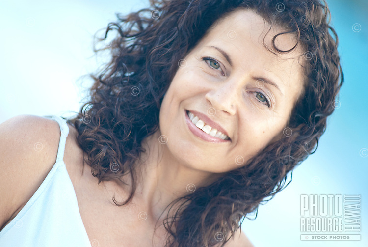 Close up portrait taken at Kailua beach of beautiful curly haired woman at age 50 wearing soft blue dress