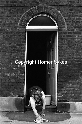 Woman cleaning her home and washing  pavement. Waterloo SE London. England. 1975<br />