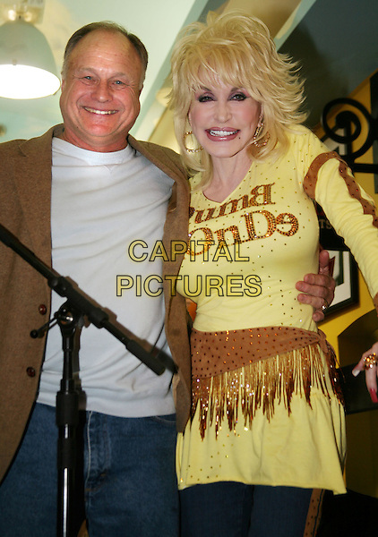"BUDDY MESSER (OWNER) & DOLLY PARTON.At the grand opening of her new store ""Trinkets & Treasures"" in downtown Nashville, TN, USA, 12th March, 2010..half length  Dumb blonde slogan top t-shirt yellow gold make-up hair wig brown tassels fringes crystals sparkly .CAP/ADM/RR.©Randi Radcliff/Admedia/Capital Pictures"