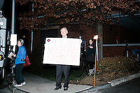 """A man holds a sign reading """"9-11-2001 / Never Forget / 500 Police Died / NYFD"""" near where supporters of Donald Trump gathered near the Sheraton Portsmouth Harborside Hotel in Portsmouth, New Hampshire, USA. At the hotel later that evening, Republican presidential candidate and real estate mogul Donald Trump received an endorsement from the New England Police Benevolent Association executive council. A small group of perhaps 20 Trump supporters stood outside the hotel and there was a larger group of anti-Trump protesters, mostly across the street. One of the protest organizers estimated that there were around 230 protesters gathered.Many protesters expressed disagreement with Trump's recent statements that he would ban all Muslims from entering the country. Trump brought up the recent shooting in San Berdardino, Calif., at the meeting."""