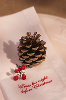 Detail of a linen napkin embroidered with 'Twas the night before Christmas' and decorated with a fir cone and holly berries