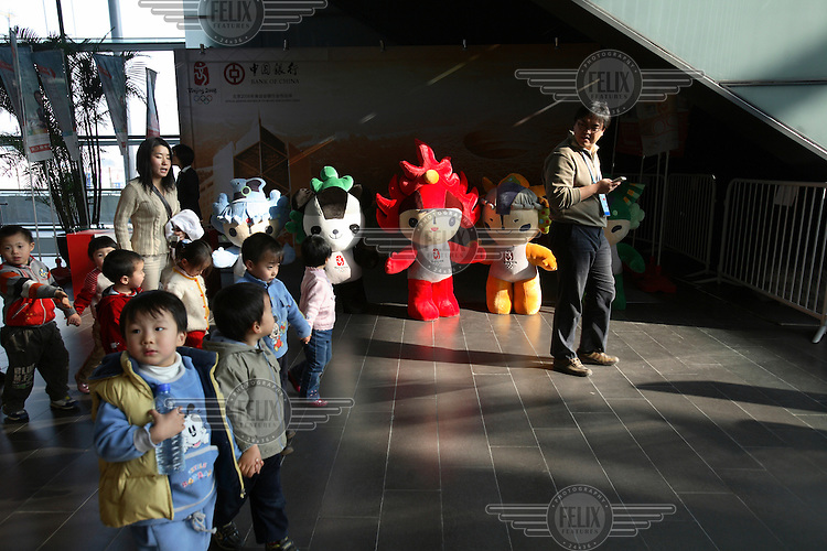 Children visit the 2008 Olympic Games venues during the 'Good Luck Beijing' preparatory event. The FUWA Olympic mascots stand in the background. ..