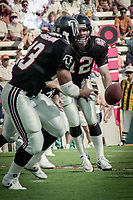 Chris Miller, #12, Atlanta Falcons, hands off to Tracy Johnson, #43, Atlanta Falcons, Atlanta Falcons at Tampa Bay Buccaneers.  The Bucs beat the Falcons 23-17  at Tampa Stadium on December 2, 1990, Tampa, Florida.  (Photo by Brian Cleary/bcpix.com)