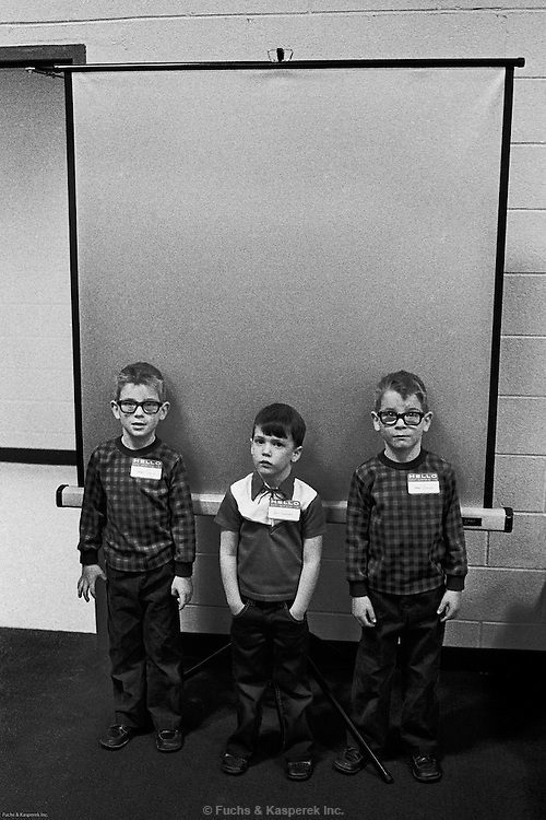A boy and two twins pose for identification photos on the first day of school. Sayreville, N.J., 1975