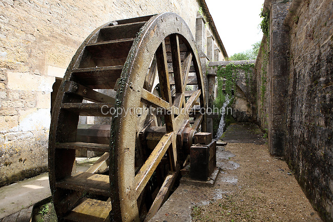 Waterwheel at the forge, Fontenay Abbey, Marmagne, Cote d'Or, France. This Cistercian abbey was founded by Saint Bernard of Clairvaux in 1119, built in the Romanesque style. The abbey itself housed 300 monks from 1200, but was sacked during the French Revolution. The 53m water-powered forge is the oldest metallurgical factory in Europe, dating from 1220. It was recently reconstructed. The monks extracted iron ore from a nearby hill and forged iron tools to sell. The Cistercians were masters of metallurgy and invented the hydraulic hammer on this site, which was driven by this waterwheel. Picture by Manuel Cohen