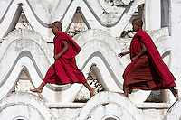 Myanmar, Burma.  Mingun, near Mandalay.  Two Young Novice Bhuddist Monks Walking on the Hsinbyume Paya, a Stupa Built in 1816.