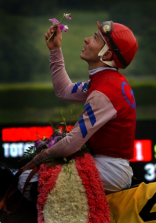 Jockey Jose Valdivia, aboard Castledale, looks up and touches a flower to the sky after winnning the $750,000 Santa Anita Derby, Saturday afternoon in Arcadia.
