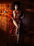 Beautiful naked woman in red kimono lying on the floor in dim dramatic light covering her nude body with an asian fan view from above
