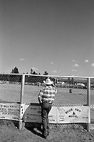 A spectator leans against a fence at the annual Lincoln Rodeo in Lincoln, MT in June 2006.  The Lincoln Rodeo is an open rodeo, which means competitors need not be a member of a professional rodeo association.