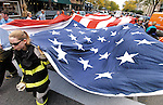 Sentinel/Dan Irving.Firefighters from several area departments carry a large US flag through downtown Holland Saturday during the annual Fire Truck Parade..(10/8/05)