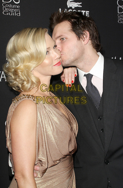 JENNIE GARTH & PETER FACINELLI.11th Annual Costume Designers Guild Awards held at The Four Season Beverly Wilshire Hotel, Beverly Hills, California, USA..February 17th, 2009.half length married couple husband wife shiny shimmery cream gold black suit jacket stubble facial hair dress grecian style draped red nail varnish polish profile kiss kissing beige.CAP/ADM/KB.©Kevan Brooks/AdMedia/Capital Pictures.