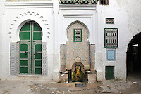 The El-Ouasaa fountain, with horseshoe arch recess and wall of traditional zellige tilework, in the medina or old town of Tetouan, on the slopes of Jbel Dersa in the Rif Mountains of Northern Morocco. Tetouan was of particular importance in the Islamic period from the 8th century, when it served as the main point of contact between Morocco and Andalusia. After the Reconquest, the town was rebuilt by Andalusian refugees who had been expelled by the Spanish. The medina of Tetouan dates to the 16th century and was declared a UNESCO World Heritage Site in 1997. Picture by Manuel Cohen