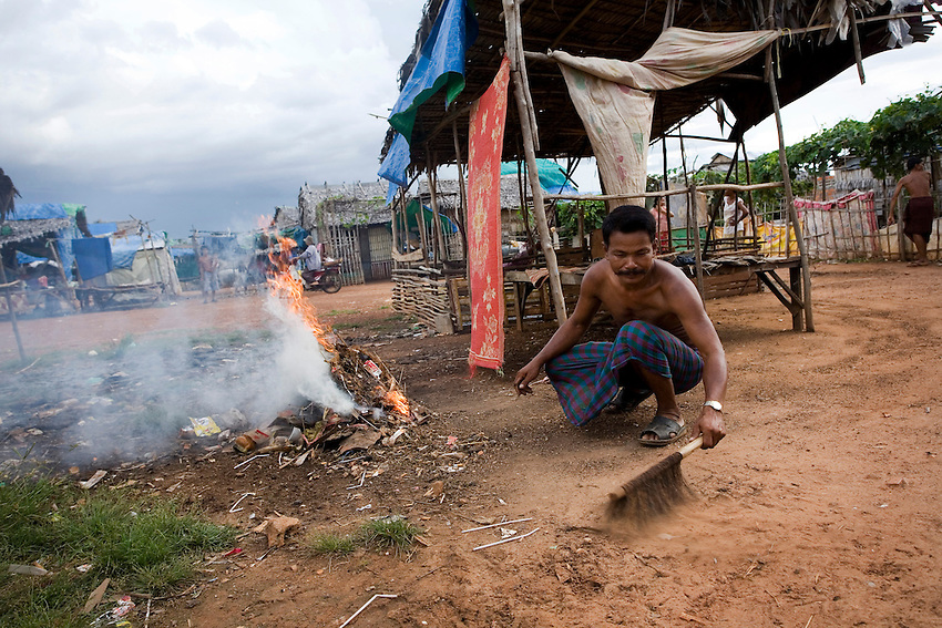 Va Savoeun, a former Dey Krahorm resident and chief of Pthas Khiev community, sweeps rubbish into a fire near a makeshift home at the relocation site provided for Dey Krahorm evictees in Phnom Bat commune, in Kandal province's Ponhea Leu district, September 9, 2010. Police and construction workers employed by local developer 7NG Group forcibly evicted Dey Krahorm's remaining 144 families and leveled their homes on January 24, 2009. The families were given 4-metre x 6-metre plots of land, on which they have build makeshift shelters of wood, mud, tarpaulin and corrugated tin. Va Savoeun said that 467 former Dey Krahorm families and vendors had been relocated to Pthas Khiev community, though only 222 families are currently residing there. The rest have returned to Phnom Penh to seek employment because there are few job opportunities at the relocation site. Following the eviction, the families were sent to live in temporary shelters in Damnak Trayeung village in Dangkor district. They were relocated yet again to Kandal province's Ponhea Leu district on December 12 of last year. Families have no way of earning a living as the relocation site os over 40 kilometeres from Phnom Penh.
