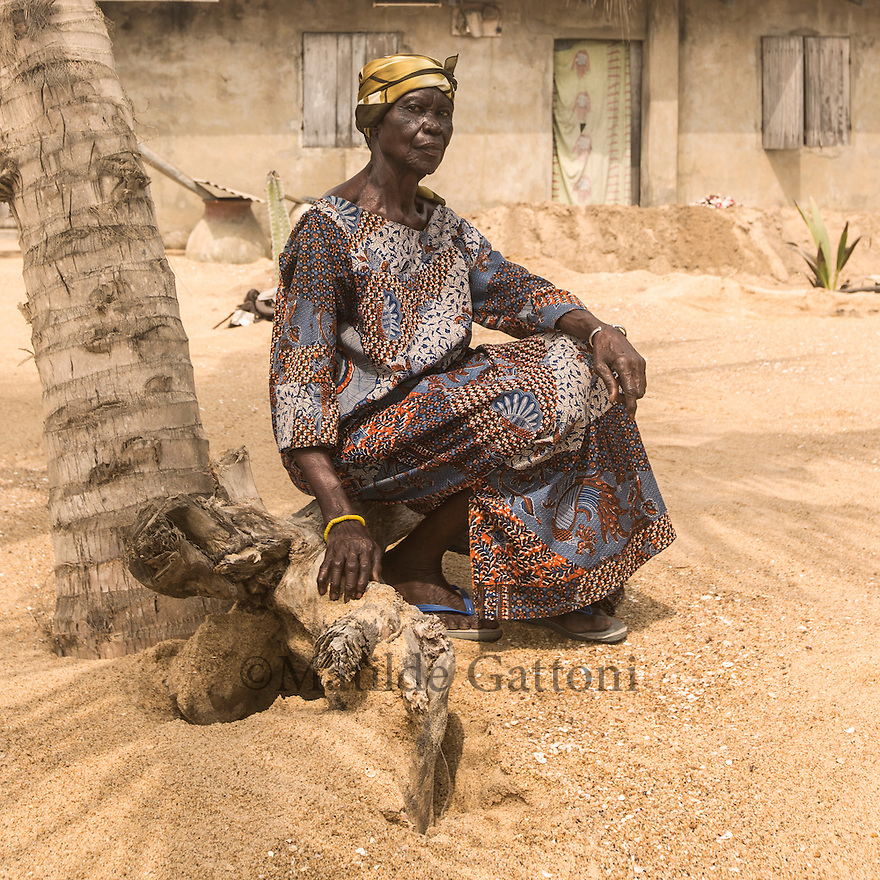 Ghana - Blekusu - Alice Kwashi, 68, posing outside her house in the village of Blekusu. The ocean has destroyed part of the old woman's house, filling it with sand and contaminating the freshwater well with saltwater. In order to prevent water from seeping into the house, the woman built a small barrier of soil just outside the entrance. « When I fall sleep, I don't know if the sea will come and take me away » she explains.