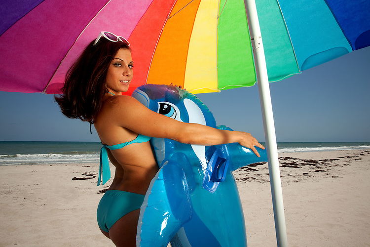 Young Brunette Woman playing with Inflatable whale on the beach