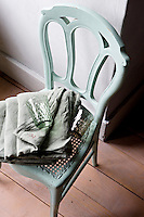 An antique bedroom chair has been painted vert-de-gris, hand-dyed sheets are near-identical in tone and a green Bohemian glass adds the finishing touch