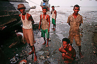 Myanmar Rohingya fishermen pause from repairing their boat at the slum near the sea in the town of Sittwe at sunset May 22, 2012. REUTERS/Damir Sagolj (MYANMAR)