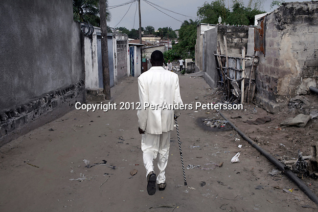 "KINSHASA, DEMOCRATIC REPUBLIC OF CONGO - FEBRUARY 12: Jika, a senior Sapeur takes a walk in his white diamond suit close to his home in the Mombele area on February 12, 2012 in Kinshasa, DRC. Jika loves Japanese fashion especially the designer Yohji Yamamoto. The word Sapeur comes from SAPE, a French acronym for Société des Ambianceurs et Persons Élégants. or .Society of Revellers and Elegant People. and it also means, .to dress with elegance and style"". Most of the young Sapeurs are unemployed, poor and live in harsh conditions in Kinshasa,  a city of about 10 million people. For many of them being a Sapeur means they can escape their daily struggles and dress like fashionable Europeans. Many hustle to build up their expensive collections. Most Sapeurs could never afford to visit Paris, and usually relatives send or bring clothes back to Kinshasa. (Photo by Per-Anders Pettersson)"