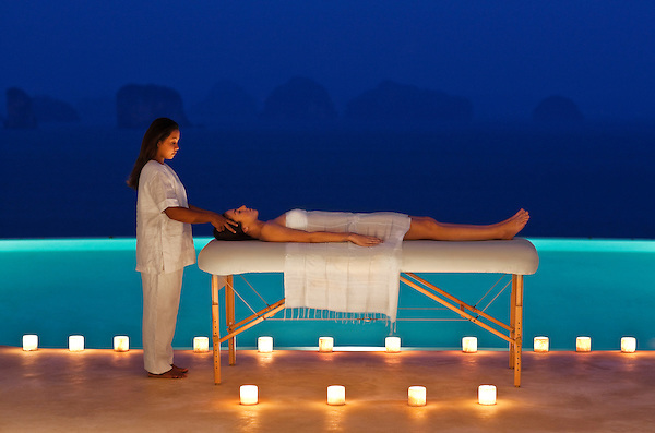 A woman receives a candlelit poolside massage at dusk at the Hilltop Reserve, a three-bedroom private pool villa at Six Senses Hideaway Yao Noi. Thailand.