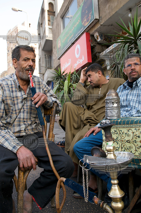 Men smoking a hookah water pipe outside a roadside cafe..