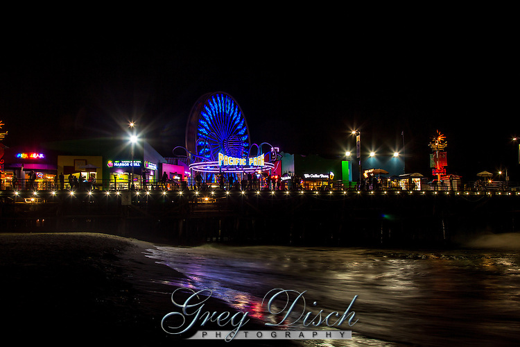 The Santa Monica Pier at night. The Santa Monica Pier is  located at the foot of Colorado Avenue in Santa Monica, California and is a prominent, 100-year-old landmark. The pier contains Pacific Park, a family amusement park with a large Ferris wheel.<br /> <br /> the current Santa Monica Pier is actually two adjoining piers that long had separate owners. The long, narrow Municipal Pier opened September 9, 1909, primarily to carry sewer pipes beyond the breakers, and had no amenities. The short, wide adjoining Pleasure Pier to the south, a.k.a. Newcomb Pier, was built in 1916 by Charles I. D. Looff and his son Arthur, amusement park pioneers.