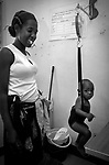 A woman weighs her child during a medical examination at the clinic of Medicos del Mundo (Doctors of the World) in Matula, where fight and educate against AIDS.