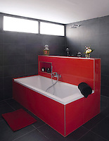 A dramatic scarlet red free-standing bath with a built-in tiled partition wall visually divides the shower area from the rest of the bathroom