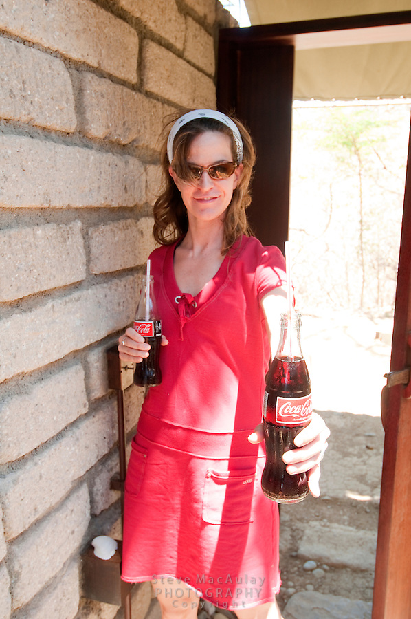 Young woman in red dress and sunglasses offers a cold Coke, Morgan's Rock Hacienda and Eco Lodge, Nicaragua