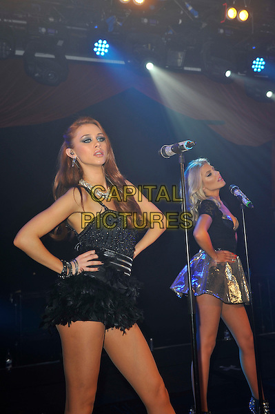 The Saturdays  - Una Healy and Mollie King.The Saturdays performing at G-A-Y, Heaven Night Club, London, England, UK, 23rd March 2013..half length music gig live on stage band girl group microphone black skirt top gold silver singing hands on hips  feather dress .CAP/MAR.© Martin Harris/Capital Pictures.