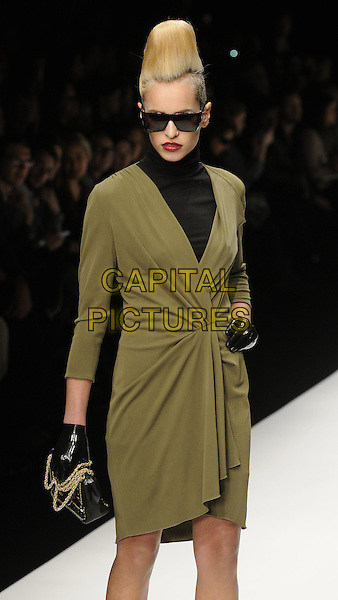 ALICE DELLAL .At the Issa Fashion Show during London Fashion Week, Somerset House, London, England, UK,.February 23rd 2010..LFW half length catwalk runway model modeling green black polo neck wrap dress leather gloves bag hand on hip hair quiff 3/4 .CAP/CAN.©Can Nguyen/Capital Pictures.