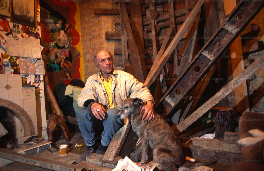 Mick and his dog. Claremont Road, Leytonstone, London. Claremont Road, ran immediately next to the Central line, and was completely occupied by protesters. The road became a vibrant squatter community full of site specific art installations. 92-year-old Dolly Watson was an original resident refused the D.O.T's offer to move. She became friends with the road protesters, who named the watchtower, built from scaffold poles, after her.<br /><br />The British Road Protesters movement began in the early 1990s when the Donga tribe squatted Twyford Down to save this beautiful site, a site of scientific interest SSI from the Ministry of transport's road building programme which threatened to destroy the landscape. The Dongas was the name of the ancient walkways, the paths trodden in the middle ages by people walking down to Winchester. A small tribe were joined by people of all walks of life who came to Twyford Down to defend it. A long hard battle over several years ended in the 'cutting' a new motorway built through this ancient monument and destroying it. <br /><br />The Road Protest movement in Britain continued for many years and more battles were fought in London against the MII both at Wanstead then in Leytonstone, and subsequently at Newbury, and in Sussex. the protesters were very inventive in their use of non violent peaceful direct action. They barricaded themselves into squats, made tree houses, tunnels and have huge demonstrations against the bailliffs, police and security who tried to force their way through the defences of this alternative environmental popular movement. Many of the roads were built eventually and many sites of great beauty lost, but the government had to stand down from its road building policy and eventually the programme was halted. the protests cost the government billions. Out of that movement grew many environmental NGOs who have to this day kept fighting for ecological and sustainable environmental solutions rather than following the cu