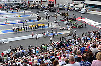 Apr. 15, 2012; Concord, NC, USA: NHRA safety safari crew, NHRA officials, fans and top fuel dragster crew members stand for the National Anthem prior to eliminations for the Four Wide Nationals at zMax Dragway. Mandatory Credit: Mark J. Rebilas-