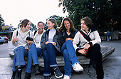 Belgrade, Serbia, Yugoslavia. Teenage girls sitting on a wooden bench laughing.