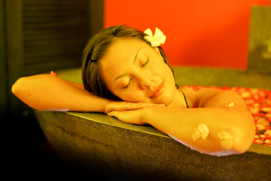 Female in a spa bath with rose petals. Bali Indonesia