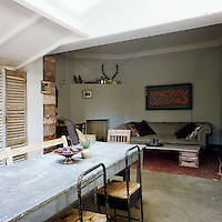 An open plan living dining area where antique pieces sit happily with reclaimed and recycled materials. The ceiling is timber-clad and the dining table is made of galvanised metal complete with bumps and holes. The concrete floor in the kitchen gives way to a wooden floor in the sitting area.