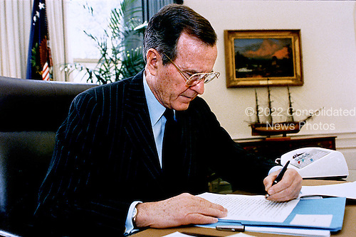 Washington, D.C. - January 24, 1992 -- United States President George H.W. Bush works on his State of the Union Address at his desk in the Oval Office in the White House in Washington, D.C. on January 24, 1992..Credit: David Valdez - White House via CNP