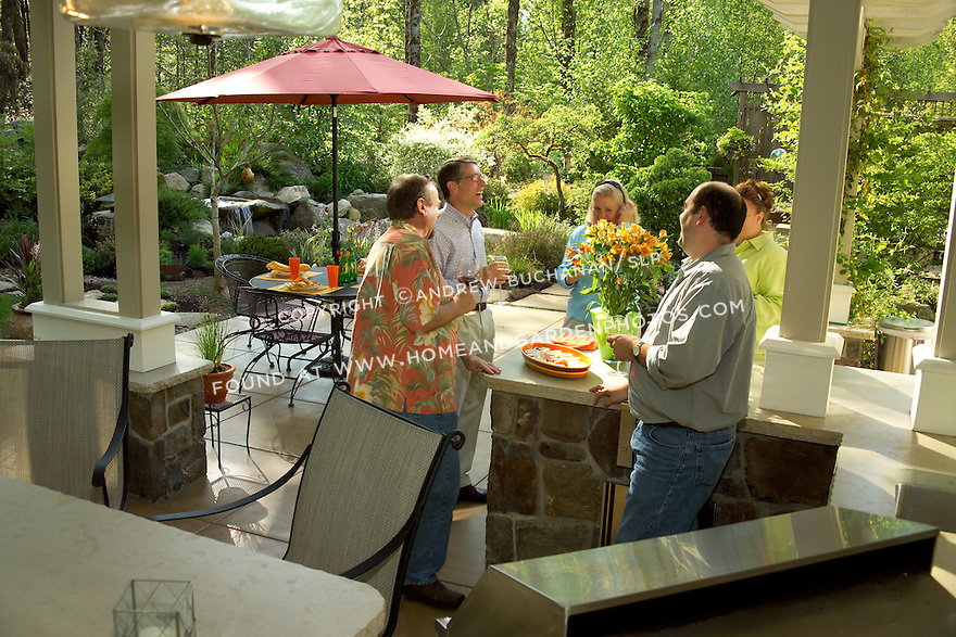 At this suburban home outside Seattle, the owners' garden designer reversed the grade of the backyard to provide privacy and create a lush, naturalistic water feature.  Then, because rain is more of a hindrance to entertaining outdoors than temperature in this moderate climate, he built a covered entertaining pavilion off the rear of the house, complete with outdoor kitchen, kitchen island, a skylighted copper-clad roof, and overhead heaters for cool fall and spring evenings.  Come visit with the owners and their designer as they entertain friends in this great indoor/outdoor space.