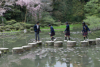 The gardens of the Heian Shrine (Heian Jingu), Kyoto, Japan in which a group of schoolchildren cross the stepping stones