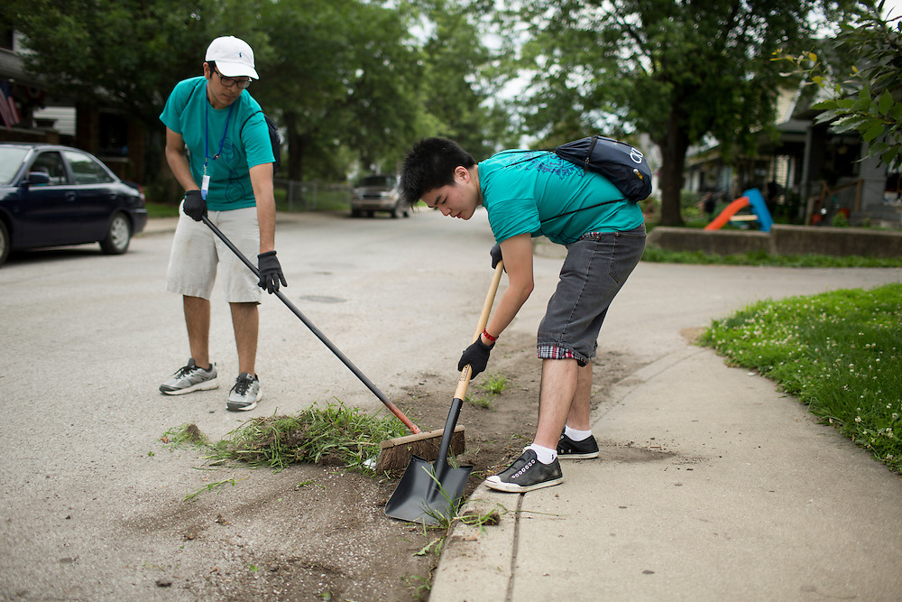 """Thomas Franco, left, and James Chen remove weeds from curbs in the Hawthrone neighborhood during """"Circle the City with Service,"""" the Kiwanis Circle K International's 2015 Large Scale Service Project, on Wednesday, June 24, 2015, in Indianapolis. (Photo by James Brosher)"""