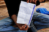 A Moroccan immigrant shows a love letter from his Spanish girlfriend, Tanger, Morocco, 22 October 2006. Every day tens of Moroccan young men try to cross ilegally the Strait of Gibraltar. ?Harraga? (immigrants in Arabic) come to Tanger from all over Morocco. They try their good luck and hidden between the wheels of a truck they attempt to board on a ferry and get to Spain, eventually further to Europe. Considering the thorough checks at the port only few of them make it. Therefore they spend months living on a beach, in huts along the walls of the port, begging for food and waiting for the right night so as their dream about Europe came true.