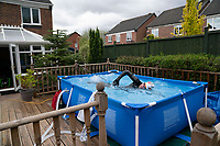 April 30th 2020, NEWCASTLE-UNDER-LYME, United Kingdom; British triathlete Lloyd Bebbington trains in a temporary swimming pool in his garden because of the coronavirus lockdown restrictions in Newcastle-under-Lyme