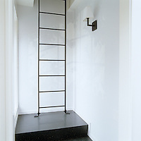 A metal ladder leads to the loft from a small landing