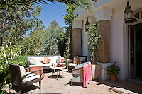 One of the sunny terraces, furnished with a suit of contemporary woven chairs and surrounded by abundant foliage