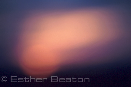The setting sun through a misty filter.