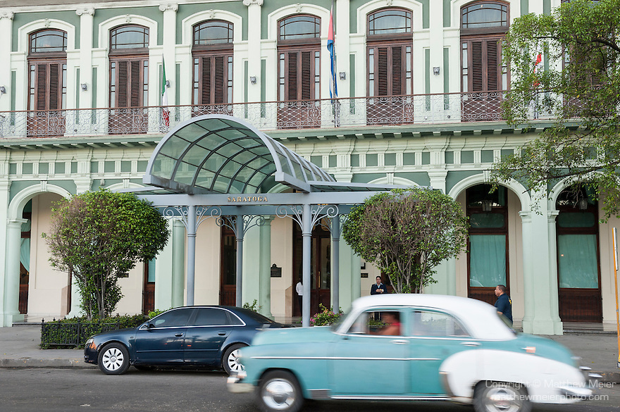 Havana, Cuba; a classic blue and white 1950 Oldsmobile driving along the Paseo de Marti past the Saratoga Hotel
